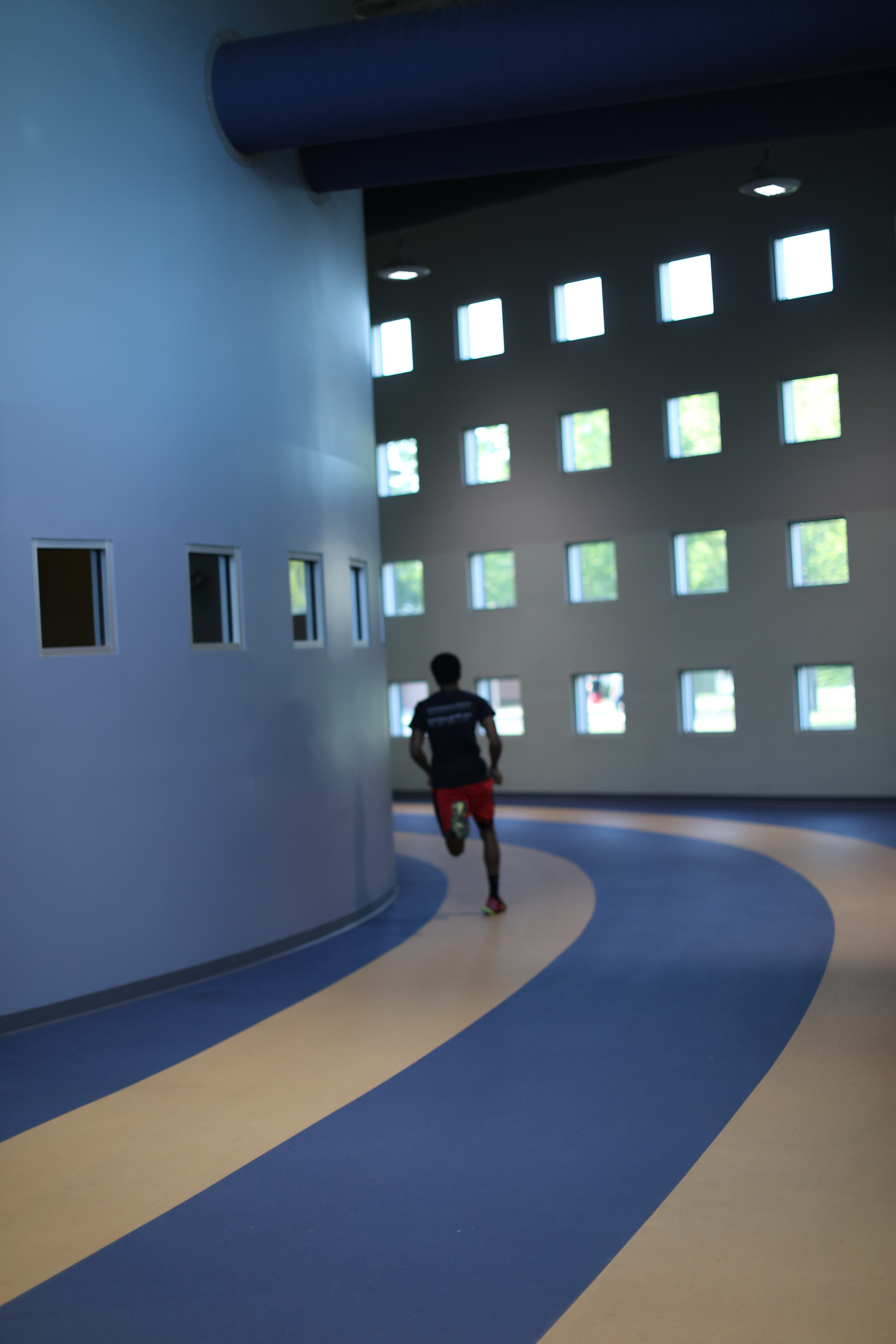 an a and t student runs on an indoor track - Campus Recreational Center